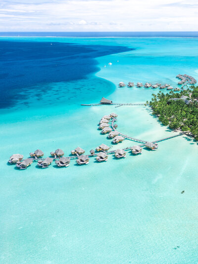 Aerial Drone view in the pacific islands, shades of blue, overwater bungalow in paradise