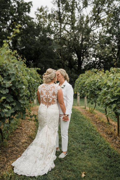 Lesbian brides kiss at The Chateau in Iowa in their vineyards