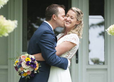 Groom kisses smiling bride on front porch at wedding in Gorham, Maine