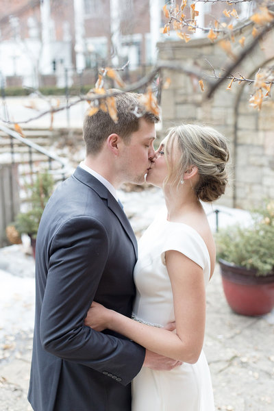 Bride and Groom share a first kiss after their first look at a snowy winter wedding at the JX Venue in Stillwater Minnesota