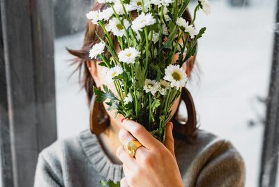 Woman holding bouquet of white flowers in front of face
