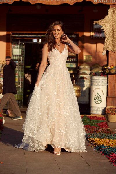 Amongst the forbidden souk markets and aromatic spices is where you will find Ainsley. Her classic, best-selling style offers brides a traditional A-line gown. The forgiving swirl of the gown gives brides a night to remember. An incredibly vibrant sequin layer is nestled under a thin tulle of botanical lace, allowing the shimmers to seep through as the sunset catches Ainsley. Her V-neckline and sheer straps are mirrored as she turns – a simple but stunning design suitable for all shapes.