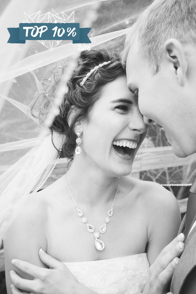 Bride and groom touching foreheads and laughing under the veil