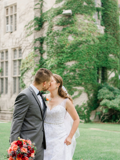 couple kissing in front of ivy lined building