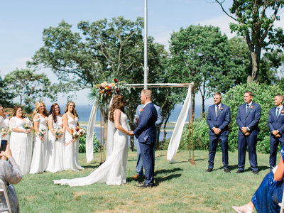 Bride and groom outdoor wedding ceremony in front of arch with corner floral arrangement