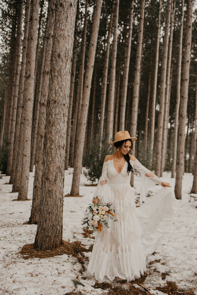 bride standing under trees with snow on the ground