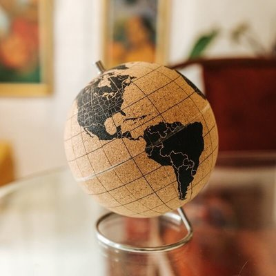 A cork world globe sitting on a glass table
