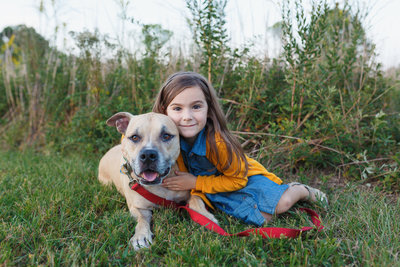 A Young Girl Embraces Her Dog During a Jacksonville Florida Family Photo Session