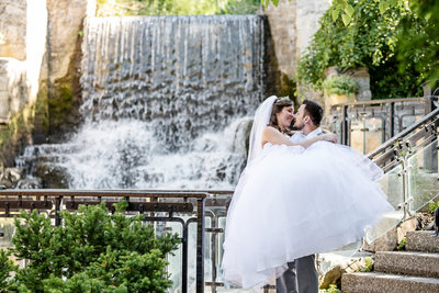 Groom holding bride in front of waterfall
