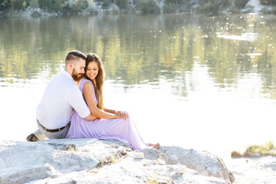 Summer Sunset Engagement Session with lavender maxi dress couple sitting on rock by water at Klondike Park in St. Louis by Amy Britton Photography Photographer in St. Louis