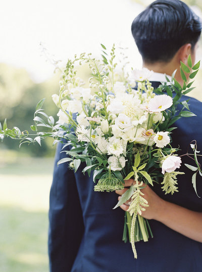 Bride hugging groom with wedding flowers