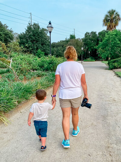 Family photographer in Charleston SC walking with a little boy and holding his hand at Hampton Park Charleston SC