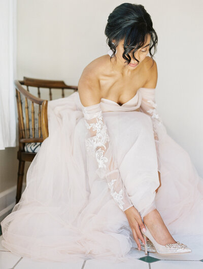 Bride sits in brown chair wearing wedding gown putting on shoe