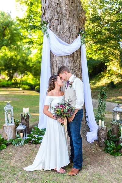 Bride and groom with beautiful bouquet under a tree