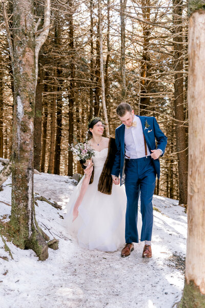 bride and groom walk in woods