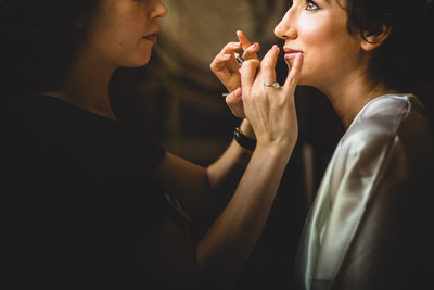 bride having her makeup done before the wedding ceremony