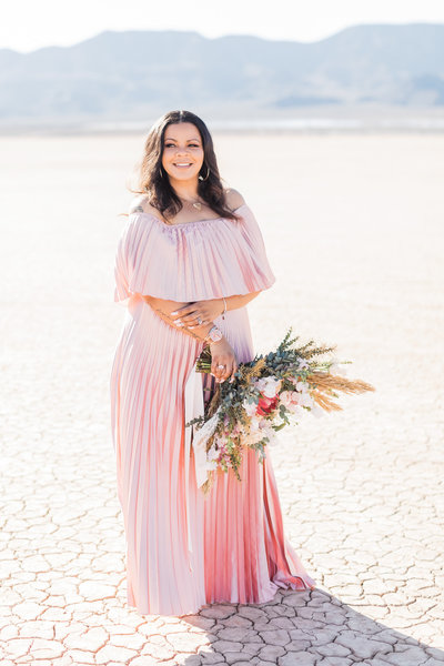 New Jersey photographer, Kiamarie Stone, smiles for photo in the desert holding a bouquet in pink full length gown