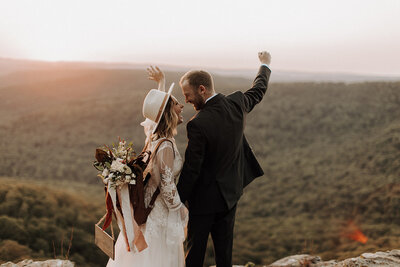 Bride and groom throwing hands up in celebration during their elopement in the mountains