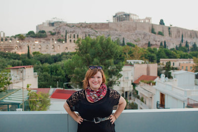Kate Timbers stands in front of the Acropolis when traveling to Athens, Greece.
