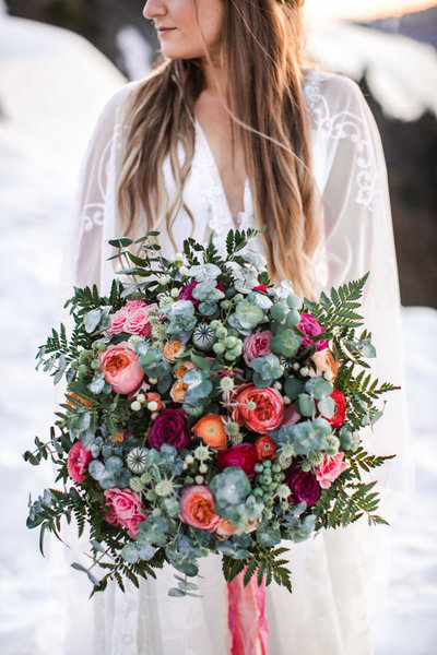 Bride holds a large floral bouquet. The bouquet contains pink and red garden roses, greenery and  ferns.  The portrait is photographed from the nose down and the bride is standing snow overlooking Crater Lake in California.
