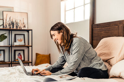 Woman working on laptop in bed learning how to build a website on Showit
