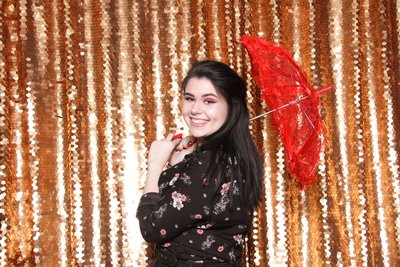 girl holding a red umbrella posing front a gold sequin backdrop
