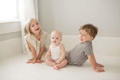three siblings sitting on the floor playing