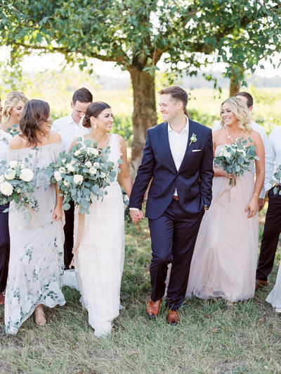 bridal party walking through a vineyard