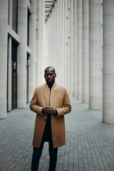 photo-of-man-in-brown-coat-posing-in-the-middle-of-a-paved-3205989