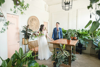 Bride leads groom through greenhouse-inspired wedding venue