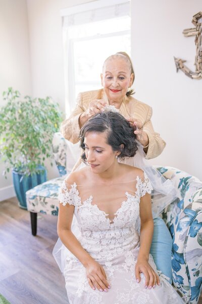 grandmother putting veil on bride