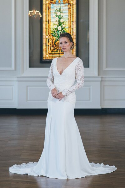 Model wearing the Bibi modern crepe and lace wedding dress with long sleeves