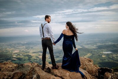 bride and groom standing on top of mountain