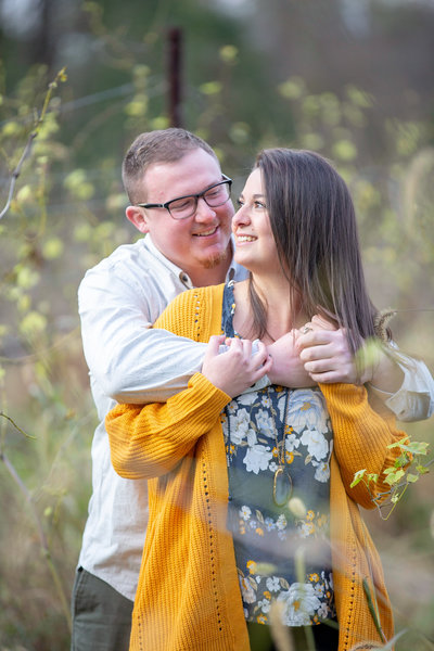 fiance embraces his soon-to-be bride from behind in a field during their engagement photography session