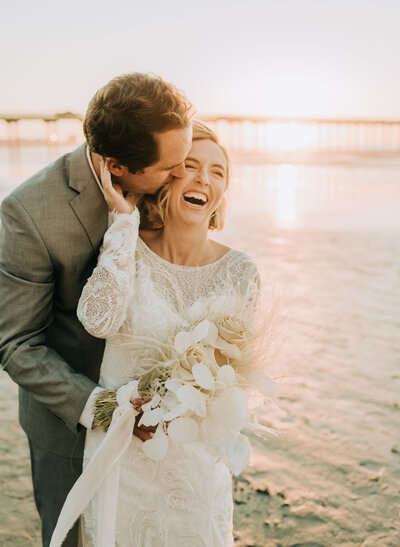 Bride and groom laughing on the beach in La Jolla on  their wedding day