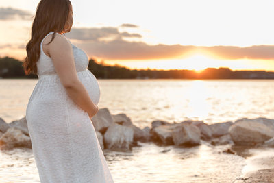 pregnant momma stands at water's edge gazing at setting sun