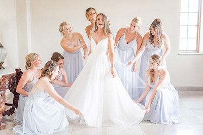 bride-getting-ready-with-her-bridesmaids-on-her-wedding-day-in-a-light-and-airy-room
