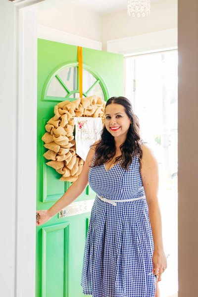 A woman in a blue gingham dress holding open a bright green door.