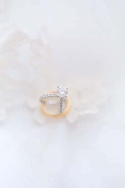 Round cut diamond and white gold engagement ring and wedding band sitting on top of men's gold wedding band and bride's lace veil taken by New Orleans wedding photographer Elizabeth Collins