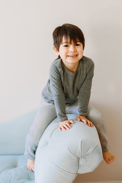 A boy straddles the arm of a light blue couch during his childrens portrait photography session
