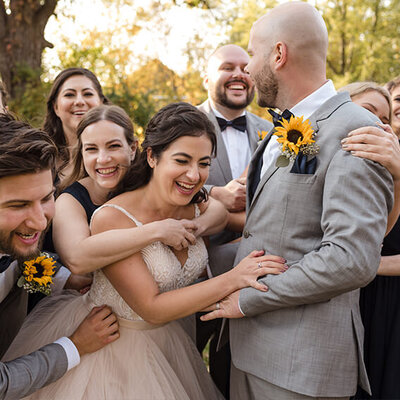 Wedding party gives bride and groom a group hug