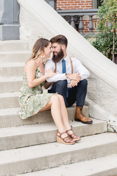 Engaged couple sit on steps and smile at each other forehead to forehead during engagement photography session
