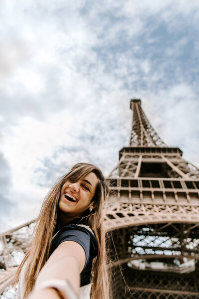 woman smiling while standing under Eiffel tower