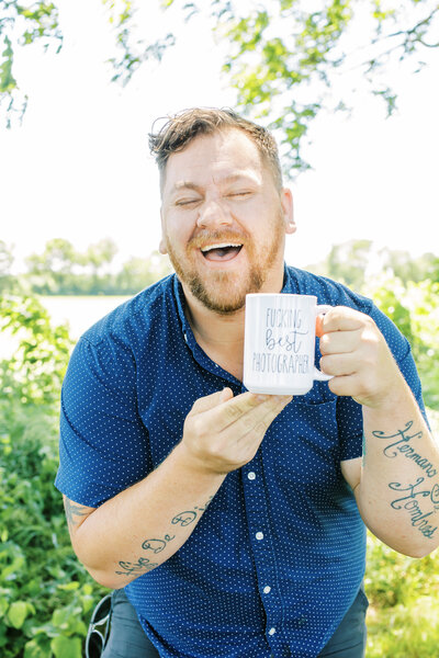 man laughing at coffee mug