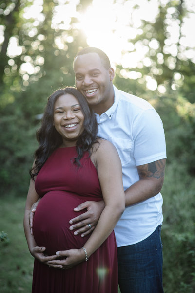 Young African American Couple Are Taking their maternity portraits as new parents Mom is in a red dress and dad is wearing a white shirt They are smiling and are surrounded by golden hour light