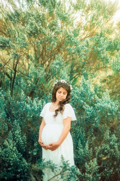 Woman in white maternity dress pososing amongst beautiful flowers in the hills of Southern California