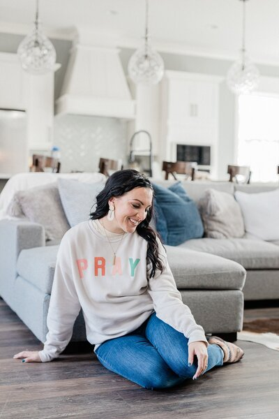 woman sitting on the floor against the couch for her personal branding photos in Nashville Tennessee and wearing a PRAY sweatshirt Dolly DeLong