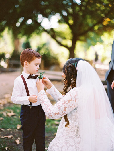 bride puts on a bouttoniere on her ring bearer on her wedding day. it is a bright photo captured on film