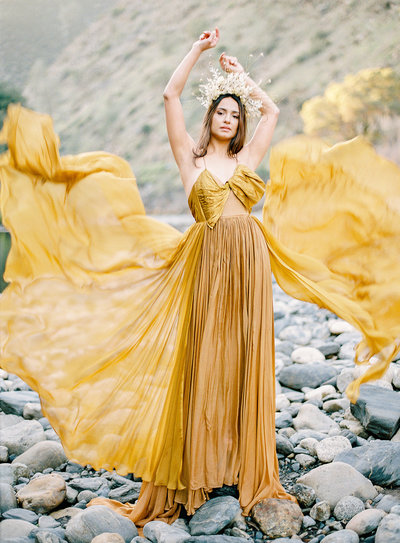 Golden yellow gown with layers floating through the air and dried floral crown on bride Photographed by Amy Mulder Photography