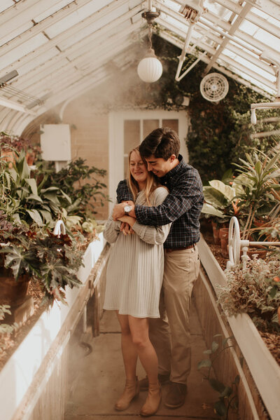 couple holding eachother in a green house